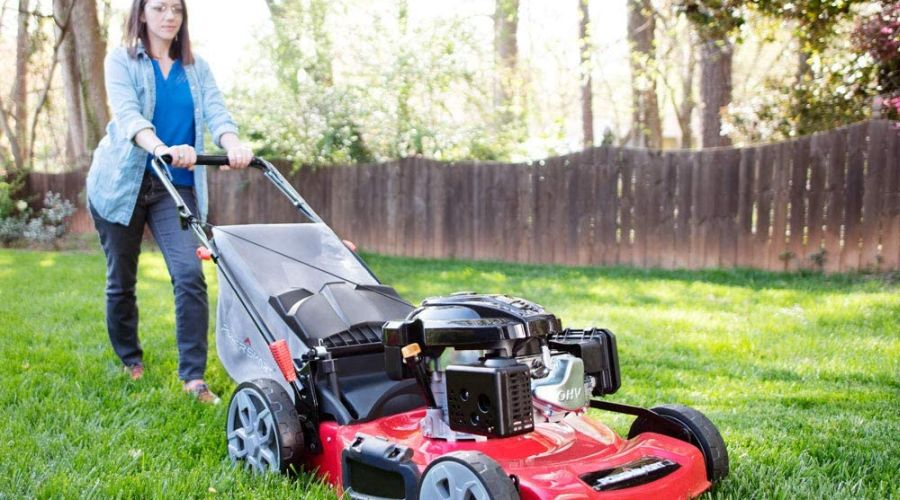 Woman using a self-propelled PowerSmart gas lawn mower.
