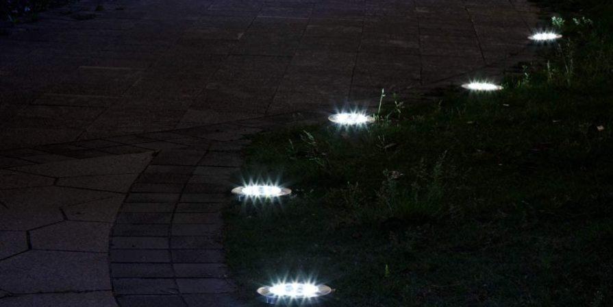 Solar disk lights illuminating a pathway at night.