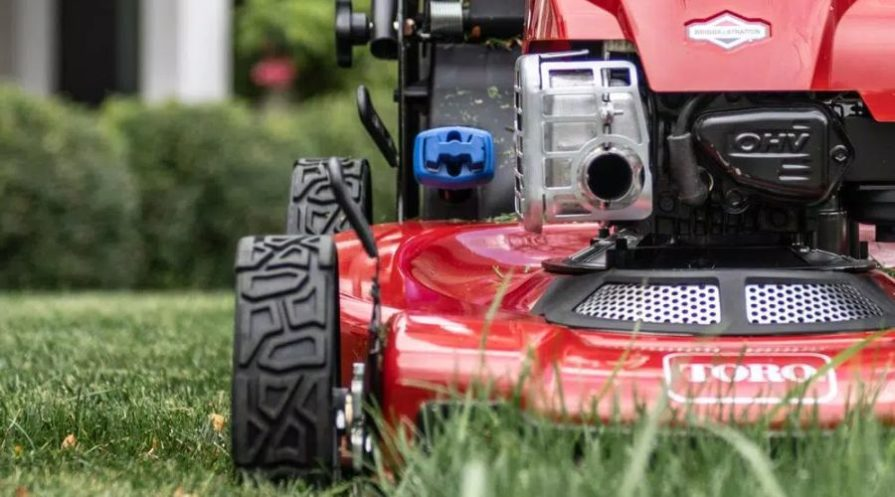 A red Toro lawn mower cutting grass on a private property.