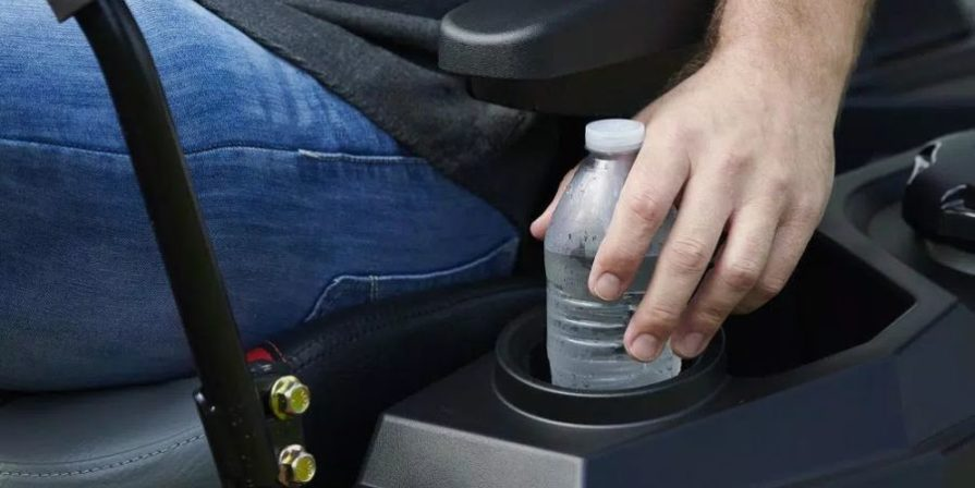 Man reaching for a water bottle sitting in the cup holder on a zero turn mower.