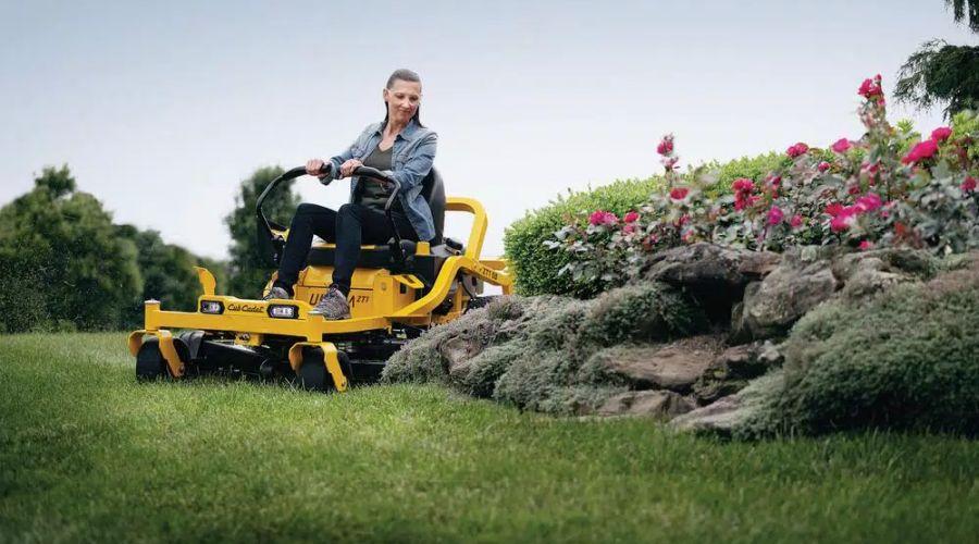 Woman steering a Cub Cadet zero turn lawn mower.