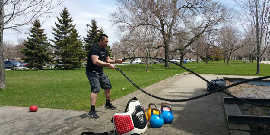 man using battle ropes for workout