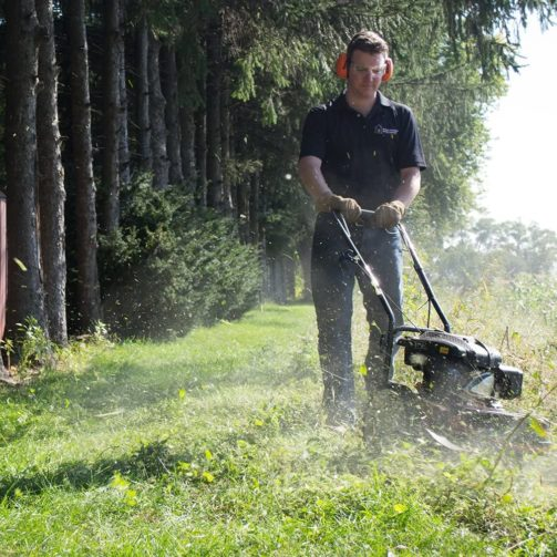 A homeowner cutting an overgown lawn with a wheeled string timmer.