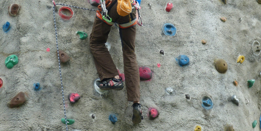 person climbing a concrete rock climbing wall