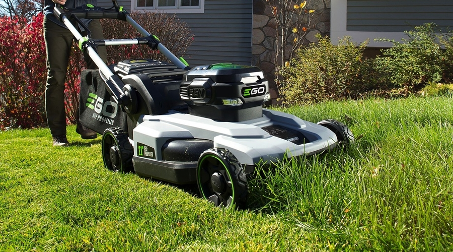 A two-tone grey and black Ego electric walk-behind mower with bright green highlights powering through an overgrown lawn with a house in the background.