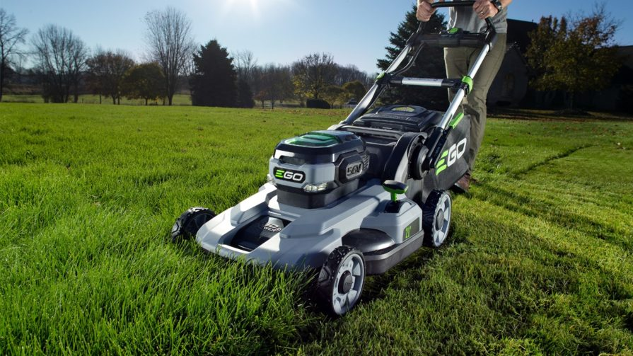 A silver and grey Ego lawn mower with a few vivd green highlights on the motor, levers, and hopper cutting tall grass in a big yard.