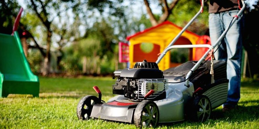 A shiny silver self-propelled lawn mower sitting on the lawn in front of some outdoor children's playground equipment.