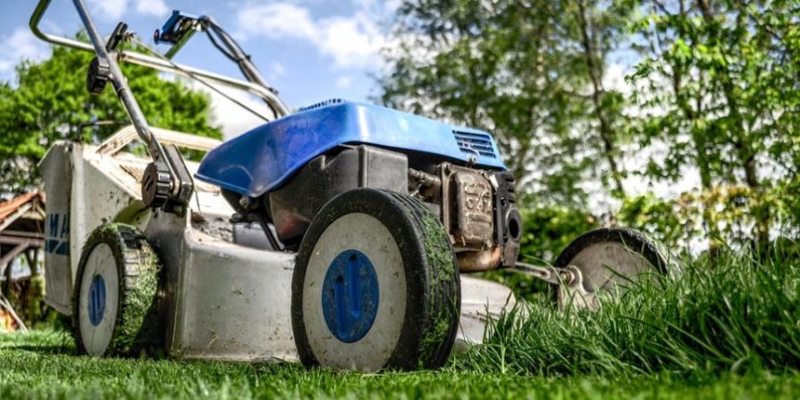 A close-up view of a silver and blue push mower cutting grass under a cloudy blue sky.