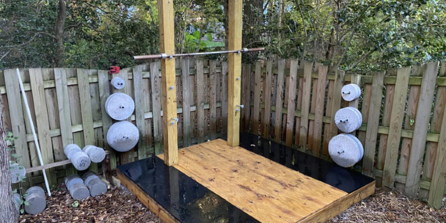 Outdoor weightlifting platform with weight plates mounted on wall