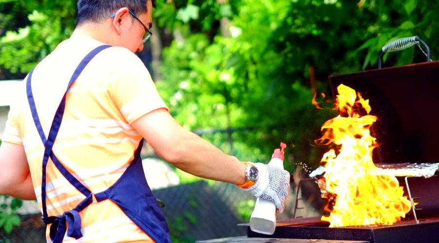 Man wearing gloves heating up the BBQ using a barbecue-safe fire accelerant.