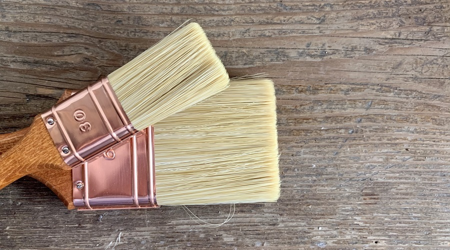 two brushes resting on wood