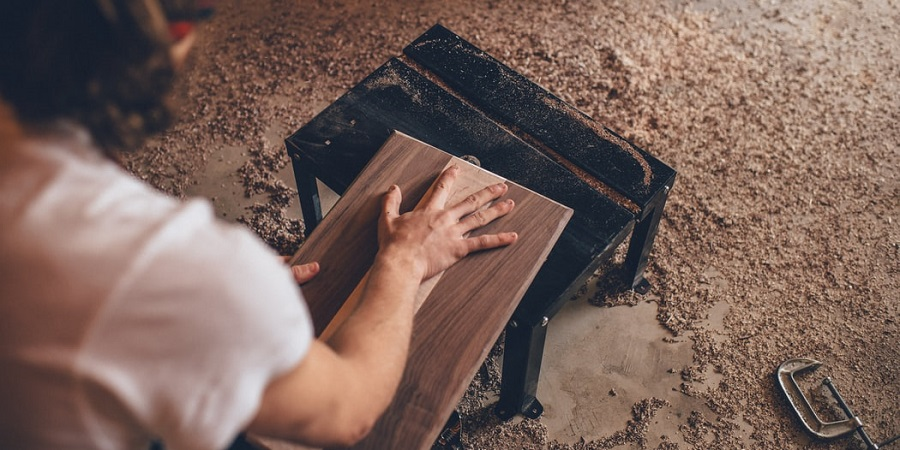 Person sanding brown plank