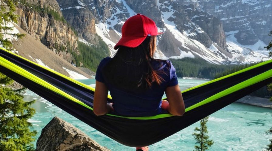 Woman sitting on a hammock with a view of blue-colored glacial water and mountains.