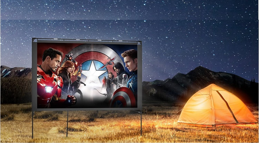 Outdoor projector screen set up next to a tent with a backdrop of mountains and a starry night sky.