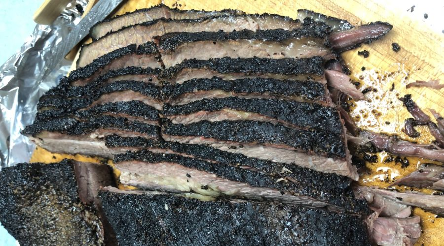 Slow-smoked, sliced brisket with salt and pepper rub bark.
