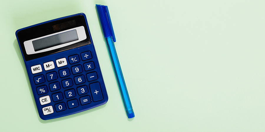 A calculator and a pen on a green background.