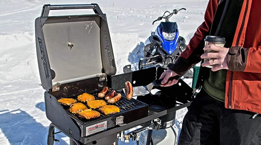 Man cooking meat on a Camp Chef BB30L grill in a winter wonderland with snowmobile in the background.