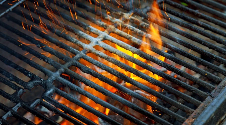 Top view of a cast iron grill grate with burning coals below.