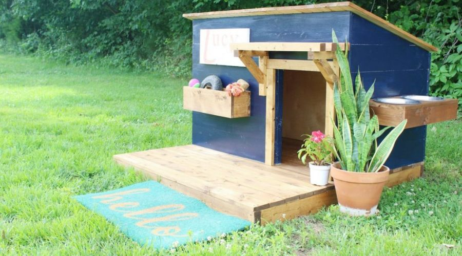 DIY Dog House With Deck sitting on a beautiful lawn.