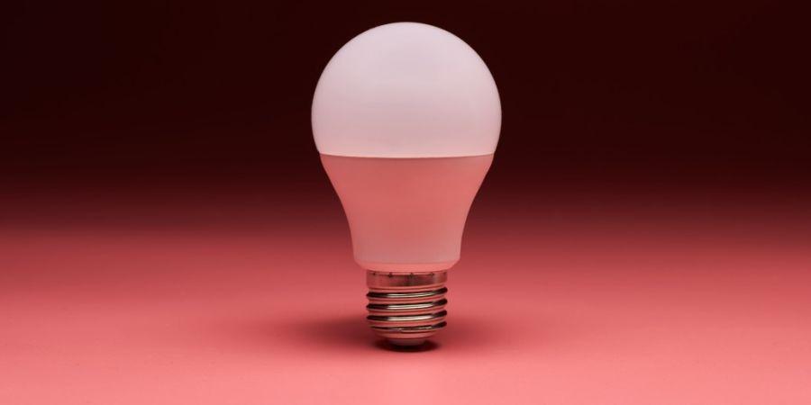 A no-heat light bulb on a red backdrop.