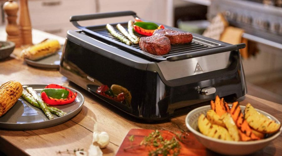A Philips infrared grill standing on a kitchen table with grilled BBQ sides next to it.