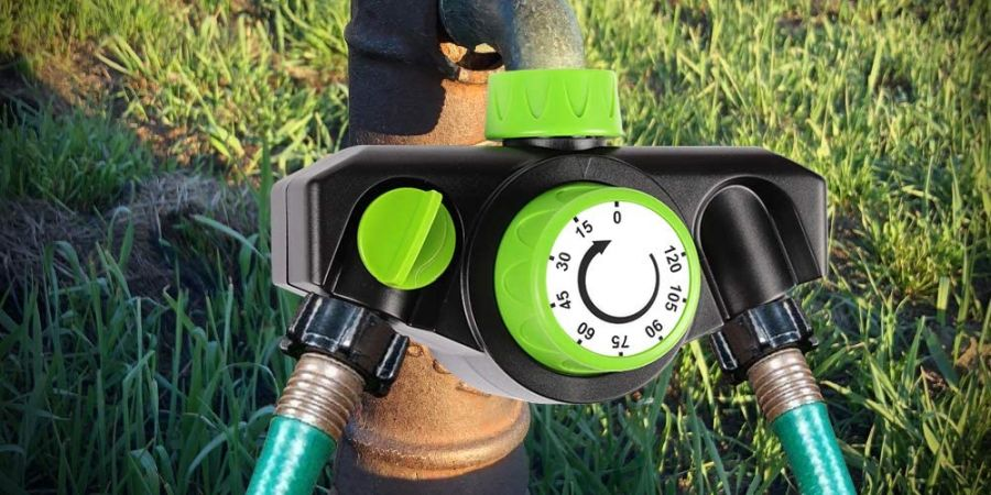 Analog mechanical watering timer by Kasonic attached to an outdoors faucet.