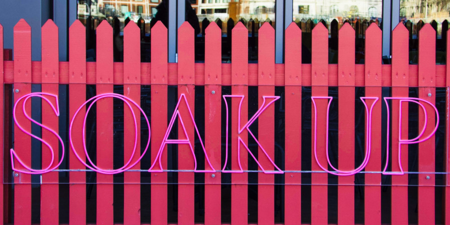 """fence painted pink with neon lettering on it """"soak up"""""""