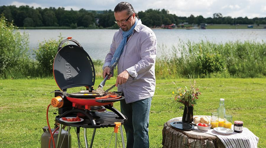 Man cooking breakfast on a Napoleon Travel Q grill by the lake shore with breakfast table set up next to him.