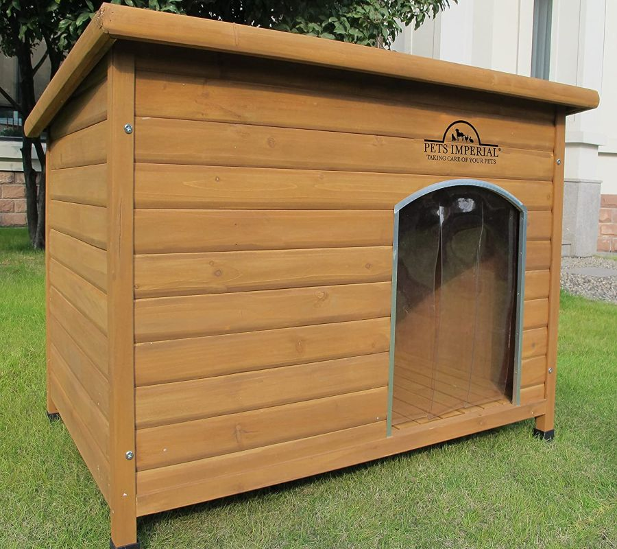 Pets Imperial Extra Large Insulated Wooden Dog Kennel standing on a lawn.