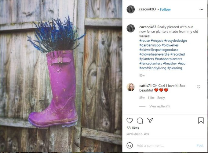purple rainboot turned into planter for purple flowers, mounted on fence