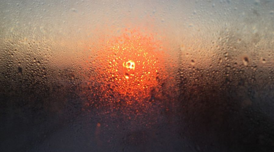 Photo of the sunset through a window covered in water droplets.