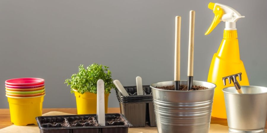 Seedling container filled with earth, small shovels and a rake for plant care, colorful plastic pots.