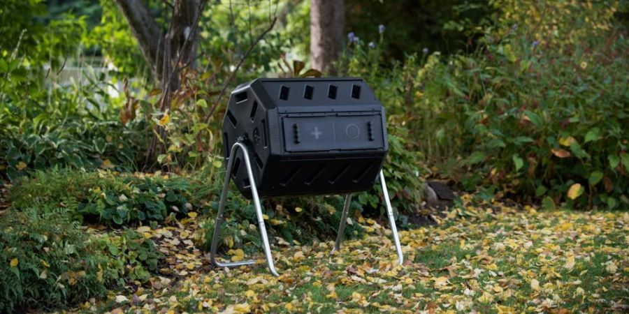 Dual chamber tumbling composter standing on lawn covered in yellow fallen leaves.