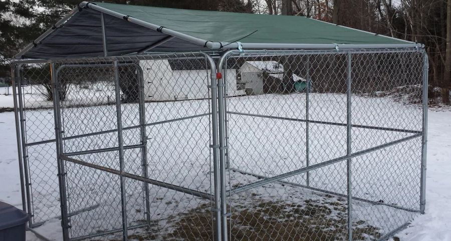 Winter-proofed outdoor dog kennel standing on snow-covered lawn.