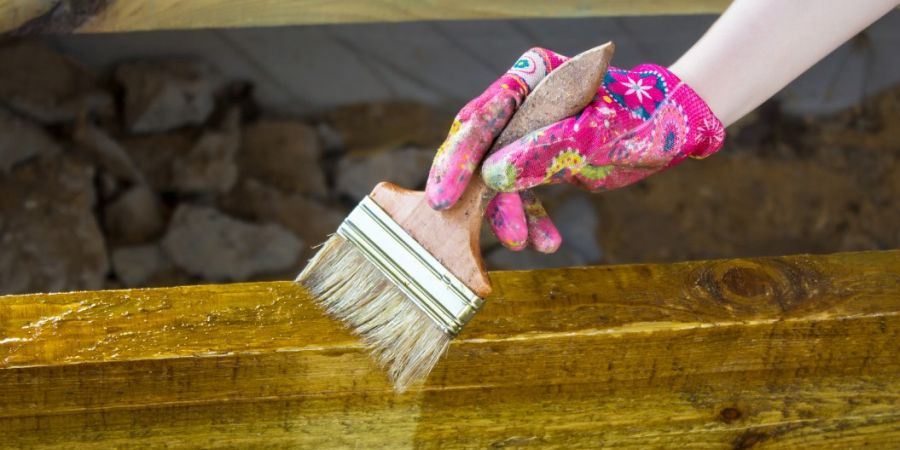 Woman wearing glove holding a brush as she's staining a beam.