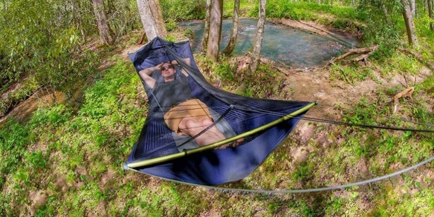 A man wearing black sunglasses, a navy blue t-shirt and brown shorts is laying in a dark blue camping hammock tent with black mosquito netting in a wooded area with a small body of water behind him.