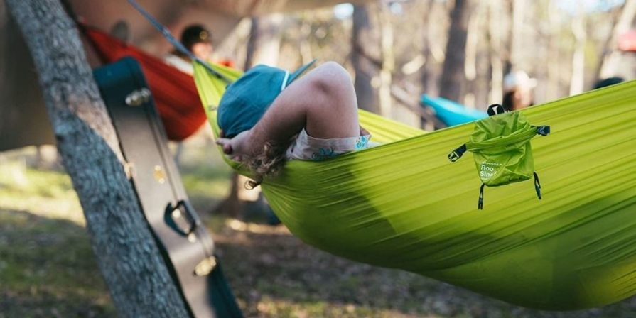 A person stretched out in a lime green parachute hammock with a guitar case leaning against a tree beside them and two other people in an orange hammock and blue hammock in the distance.