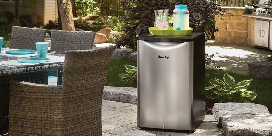 A black and stainless steel outdoor refrigerator sitting on a stone patio space with a tray holding glasses and a juice pitcher sitting on top.