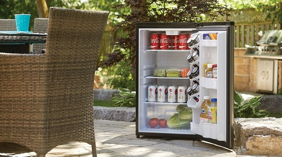 A refrigerator sitting outdoors on a patio, next to a table and wicker chairs.