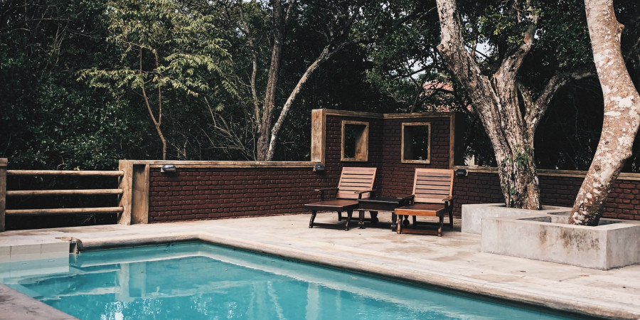 half wall of brick and wooden bars around pool with lounge chairs