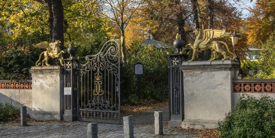 grand entrance gate with griffins perched on concrete fence
