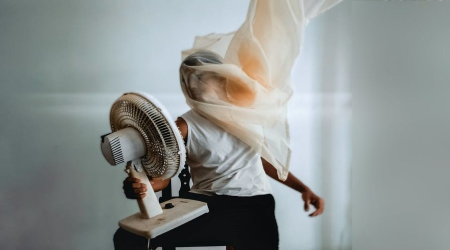An overheated man hold an oscilating fan in front of his face, he has a sheet covering his face and chest.