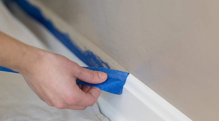 Man pulling off blue painters tape from a freshly painted wall.