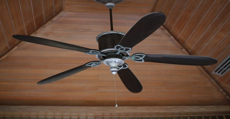 A ceiling fan with five blades and a single light bulb, brown in color.