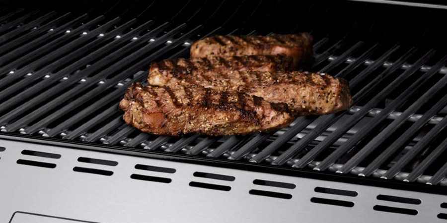 steaks searing on a grill