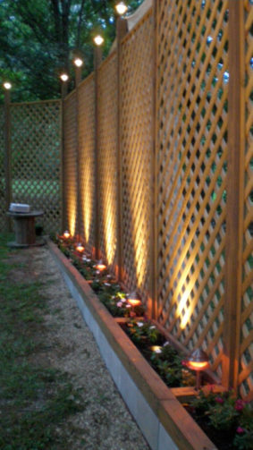 lit up lattice fence with flower boxes
