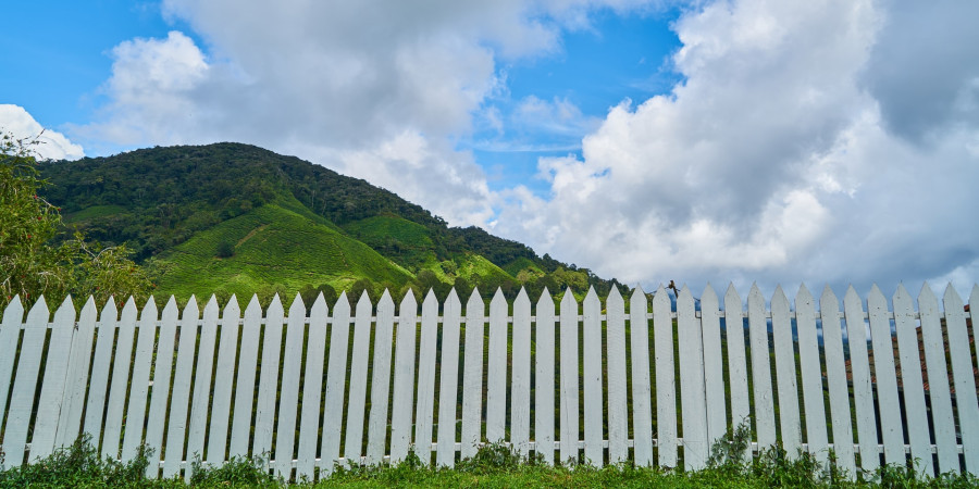 white picket fence with large green hills in background