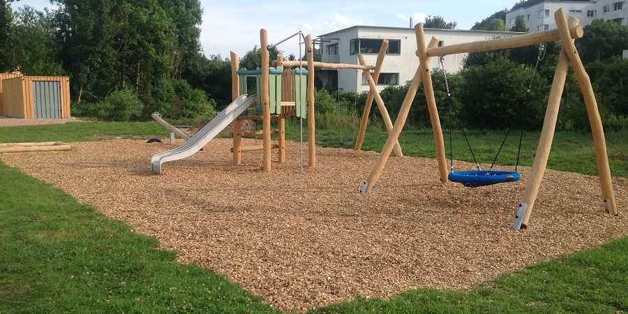 brown and blue swings on playground mulch