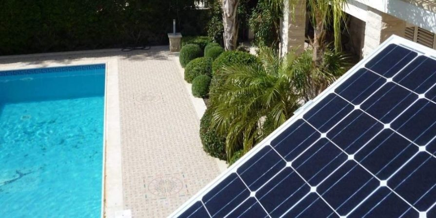 A solar panel outdoors in the sunshine, sitting with an indoor pool and pool patio below it