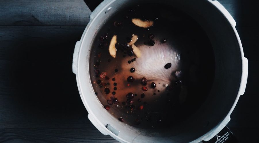 Turkey brining in a pot with spices swimming on the surface.